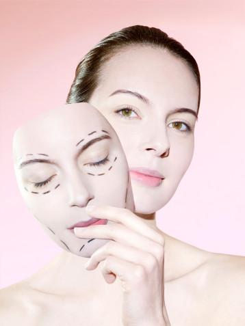 Paris. Montage photographique : visage d'une femme tenant un masque de son propre visage surquel figure un tracé de chirurgie esthétique.